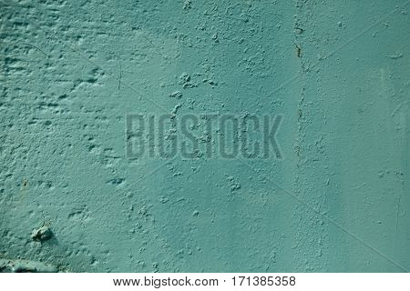 Teal color rough textured painted wall background. Abstract grunge blue uneven surface