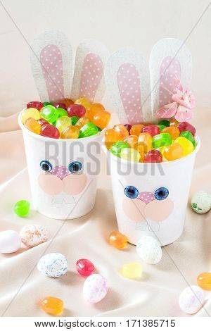 Paper cups in the form of funny Easter Bunny with candy. Homemade applique on paper cups. The idea for children gifts. DIY concept for the celebration of Easter. Vertical