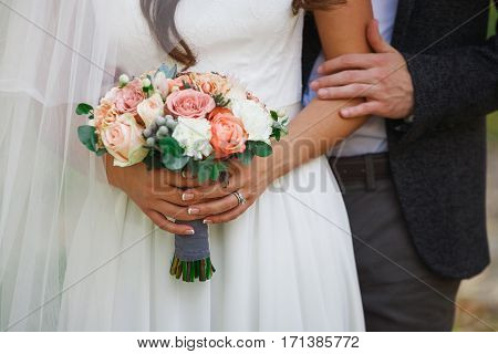 Groom and bride cropped image. Wedding bouquet from rose flowers in unrecognizable woman's hands. Happy couple