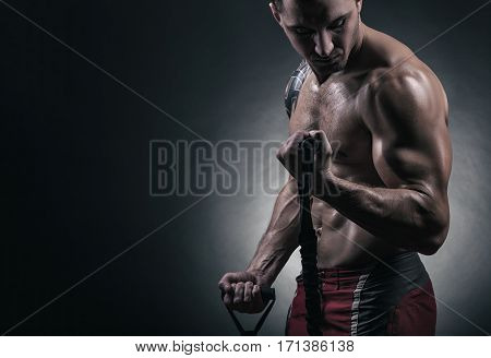 Handsome young man exercising with rubber band against a dark background