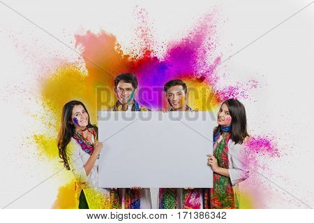 indian people celebrating holi with colours in thali and colour splash