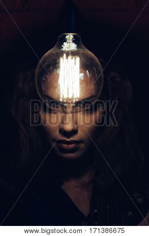 Mysterious photo of woman with light bulb. Portrait in the dark. Dangerous girl.