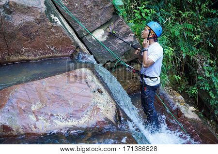 Beaufort,Sabah,Malaysia-Jan 28,2017:Adventure man taking picture with camera on selfie stick during rappelling Jempangah waterfall in Beaufort,Sabah,Borneo.