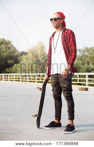 Picture of young dark skinned man wearing sunglasses holding the skateboard. Against the nature background.
