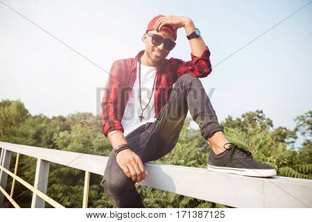 Photo of cheerful dark skinned guy touches his head and wearing sunglasses. Sitting against nature background. Looking at the camera.