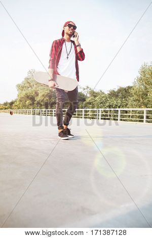 Photo of young dark skinned boy wearing sunglasses and cap holding skateboard and talking on his phone. Against the nature background.