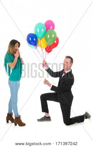 Man is doing a proposition de marriage with balloons and ring