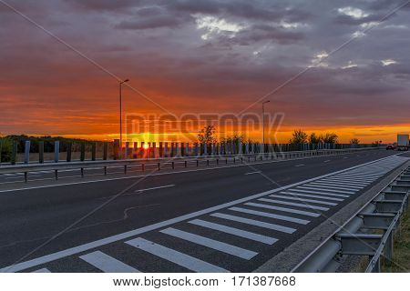 Sunset On The Highway. Beautiful sun rising sky with asphalt highways.