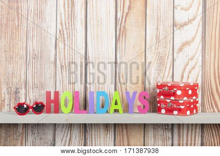 wooden background for holidays with suitcases and sunglasses