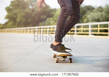 Photo of young dark skinned man skateboarding. Against the nature background.