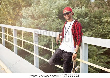 Picture of cheerful dark skinned man wearing sunglasses holding skateboard. Against the nature background.