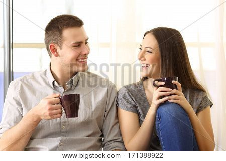 Front view of a happy couple talking and drinking coffee sitting on the floor near a window at home