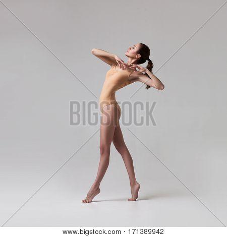 young beautiful ballet dancer in beige swimsuit posing on light grey gradient studio background