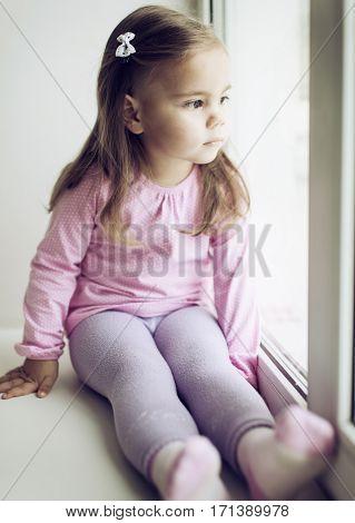 Upset little girl looking through the window