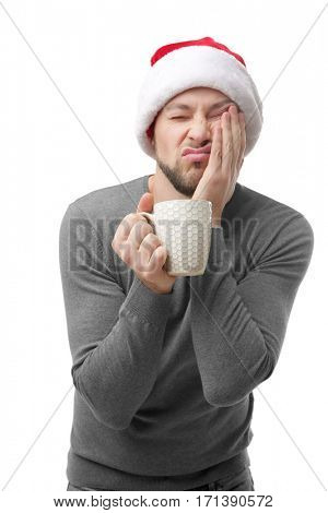 Sleeping guy in Xmas hat holding cup with coffee and propping cheek by hand on white background