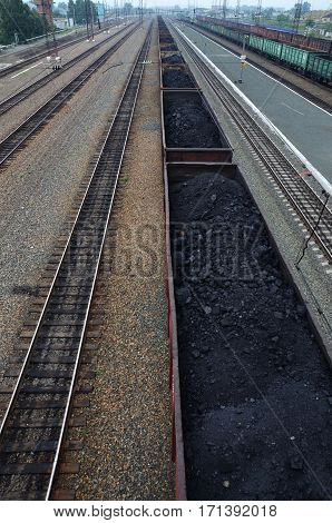 a train of wagons with coal black standing on railroad tracks
