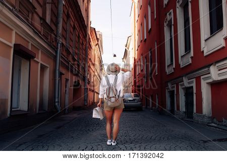 Travel guide. Young female traveler with backpack and with map on the street. Travel concept
