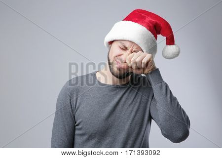 Sleepy guy in Xmas hat rubbing eyes on light background