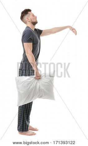 Young sleepy man suffering from somnambulism on white background