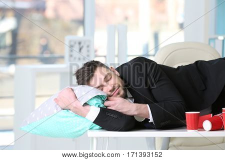 Tired business man sleeping among empty paper coffee cups on worktable in office