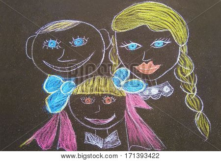 Creative chalk drawing on the asphalt of children in the family of different ages.