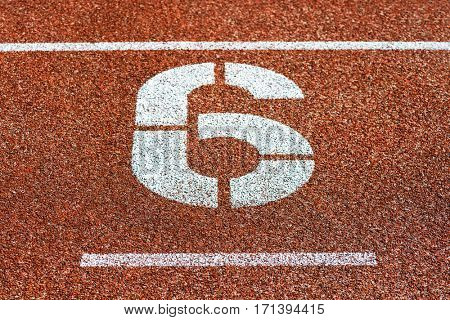 Start number six at cinder track of track and field running track