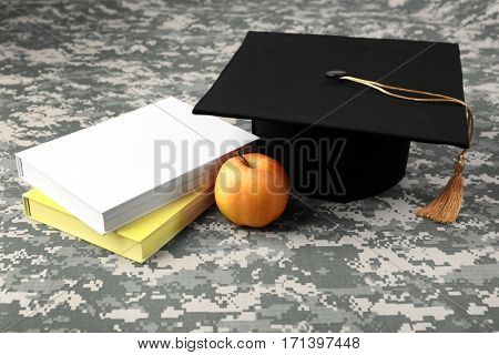 Graduation hat, apple and books on camouflage background