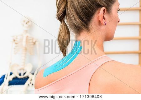 Woman from behind with Kinesio tape on shoulder in physiotherapy