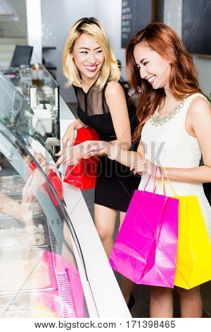 Two stylish young Asian women carrying colorful shopping bags buying food in a delicatessen standing in front of a glass display making a selection