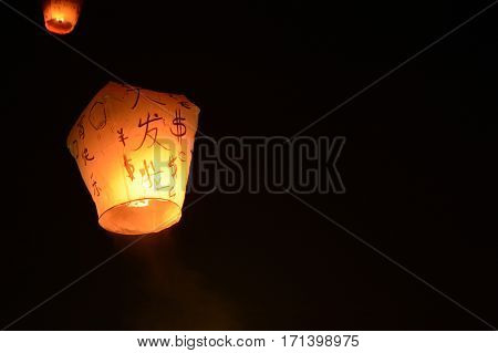 Sky lantern floating into the night sky at the festival in Pingxi, the Chinese text is a wish for money in the New Year