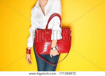 Fashion concept. Young woman holding red handbag on yellow background, closeup