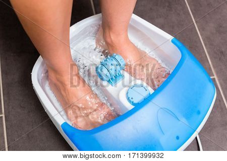 Feet of woman in foot bath on tilework bathroom floor