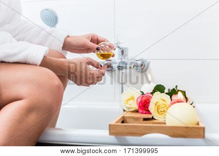 Woman preparing wellness bath with flowers, candles and fragrance oil in tub