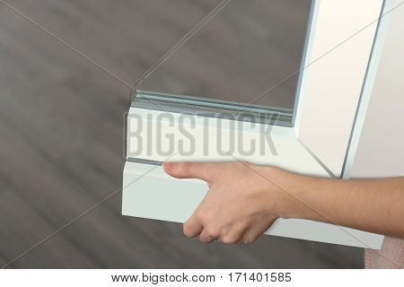 Woman holding sample of window profile, closeup