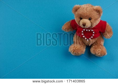 Teddy bear soft toy on blue background Love card concept with copy space. Valentine's day theme