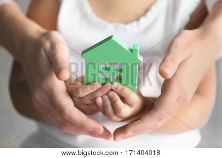 Child and adult person holding figure in shape of house, closeup. Adoption concept