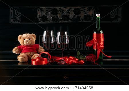 Wine bottle and two wineglasses decorated with red rose teddy bear toy and ribbon on a dark background. Valentine's day theme concept