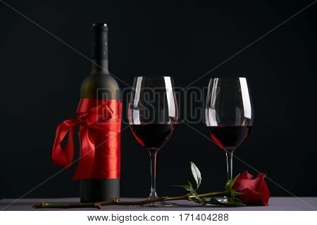 Wine bottle and two wineglasses with red rose on a dark background. Valentine's day theme concept