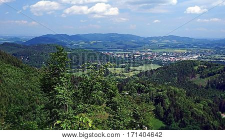 Frenstat pod Radhostem city with hills around and blue sky with few clouds during descend from Velky Javornik hill in Moravskoslezske Beskydy mountains