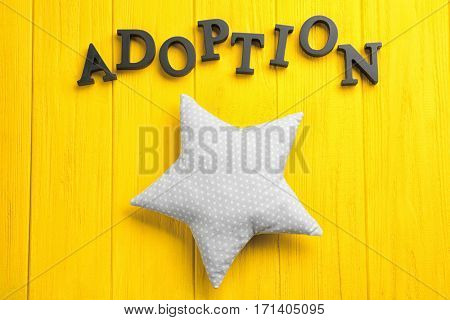 Word ADOPTION and rag star on color wooden background