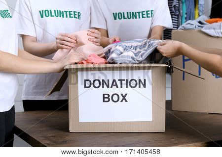 Female volunteers preparing donation box with clothes
