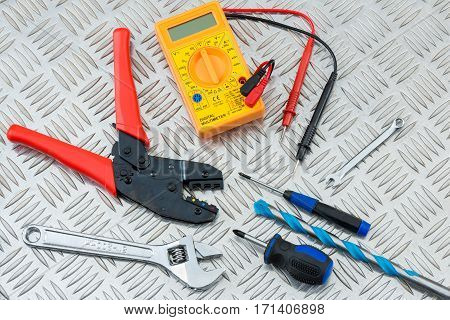 Electrician's Tools And Equipment On Metal Checker Plate
