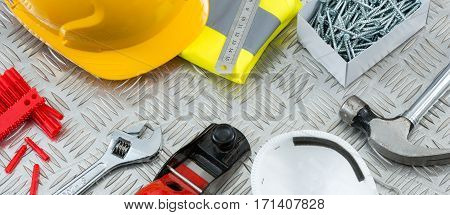 Construction or DIY tools and safety gear including a hammer a spanner hand plane face mask rawl plugs screws a hard hat and a folded vest on a steel tread plate