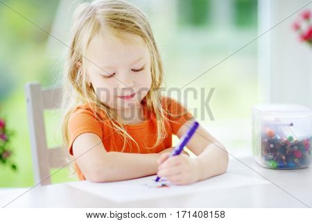 Cute Little Girl Drawing With Pencils At A Daycare. Creative Kid Painting At School. Girl Doing Home
