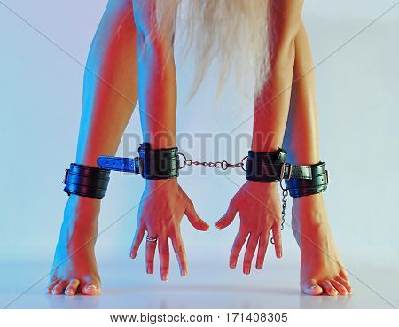 Sexy long female legs barefoot on tip-toes in leather cuffs chained together with hands in leather cuffs against colorful texturized background