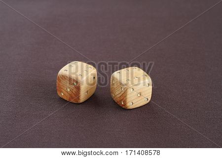 Two wooden dices with number six on the top on purple cloth