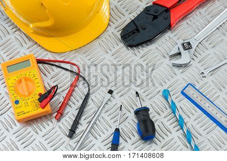 Carpentry and electrical equipment including screwdrivers a multimeter hard hat a wire stripper wrenches a metal rule and a drill bit on a steel checker plate.