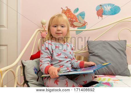 Little Girl In Pajamas Holding A Storybook In Bed