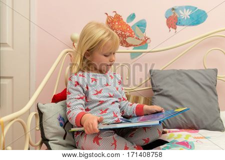 Toddler In Pajamas Reading A Storybook In Bed
