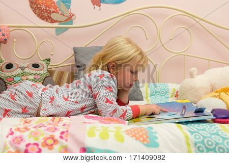 Little Girl Reading A Storybook In Bed